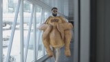 A man in roast chicken costume at the airport