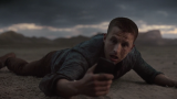 A man is lying in the desert looking at his cell phone