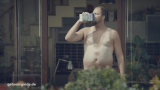 Topless man drinks from a milk carton