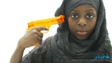 A girl holding a water gun at her head