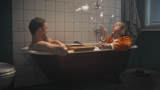 Two man sit in a bathtub.