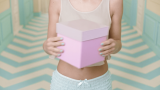 A woman in pajamas holds a jiggling box