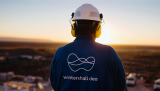 A wintershall dea employee stands before sunrise