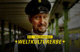 Smiling conducter from the BVG at a station with the title: