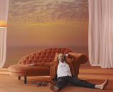 A man casually leans against an orange couch.