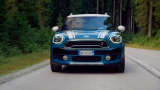 A blue Smart Mini car driving  on a street through the forest.